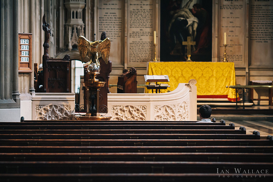 Solitary boy sat in the pews at St Luke's church, waiting for the ceremony