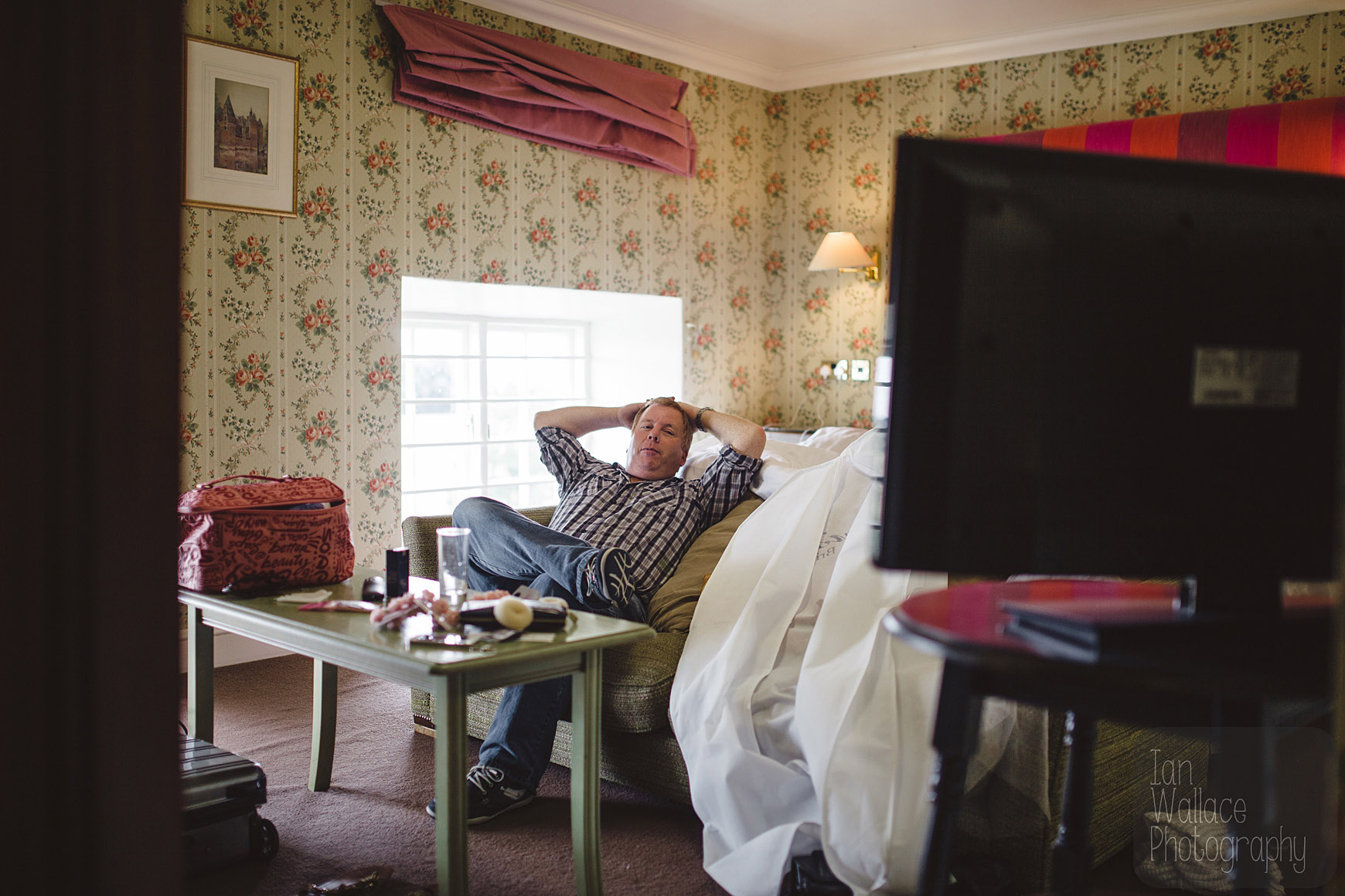 Father of the bride relaxing, watching TV during bridal preparation