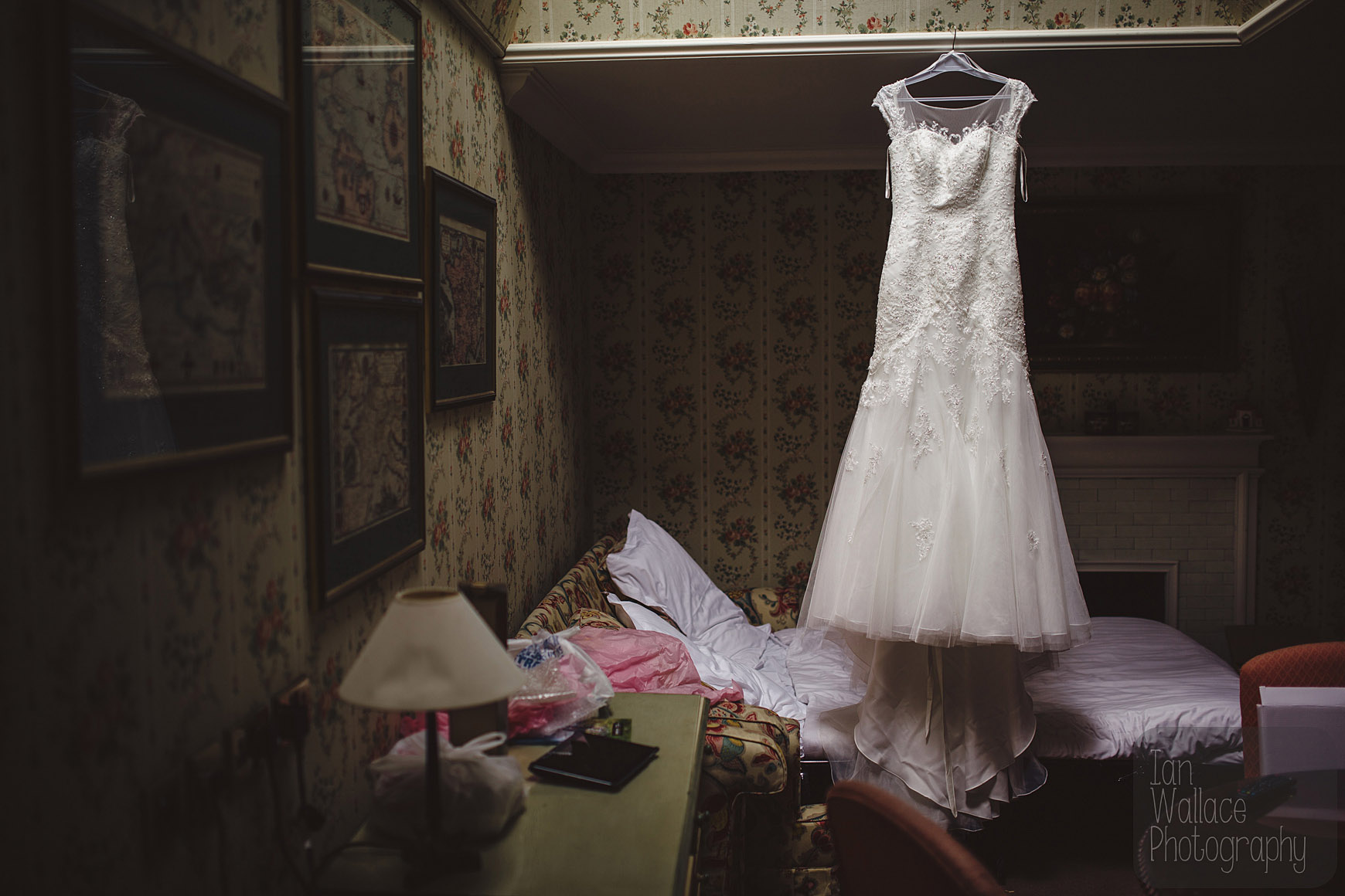 Beautifully lit wedding dress hanging in a messy room