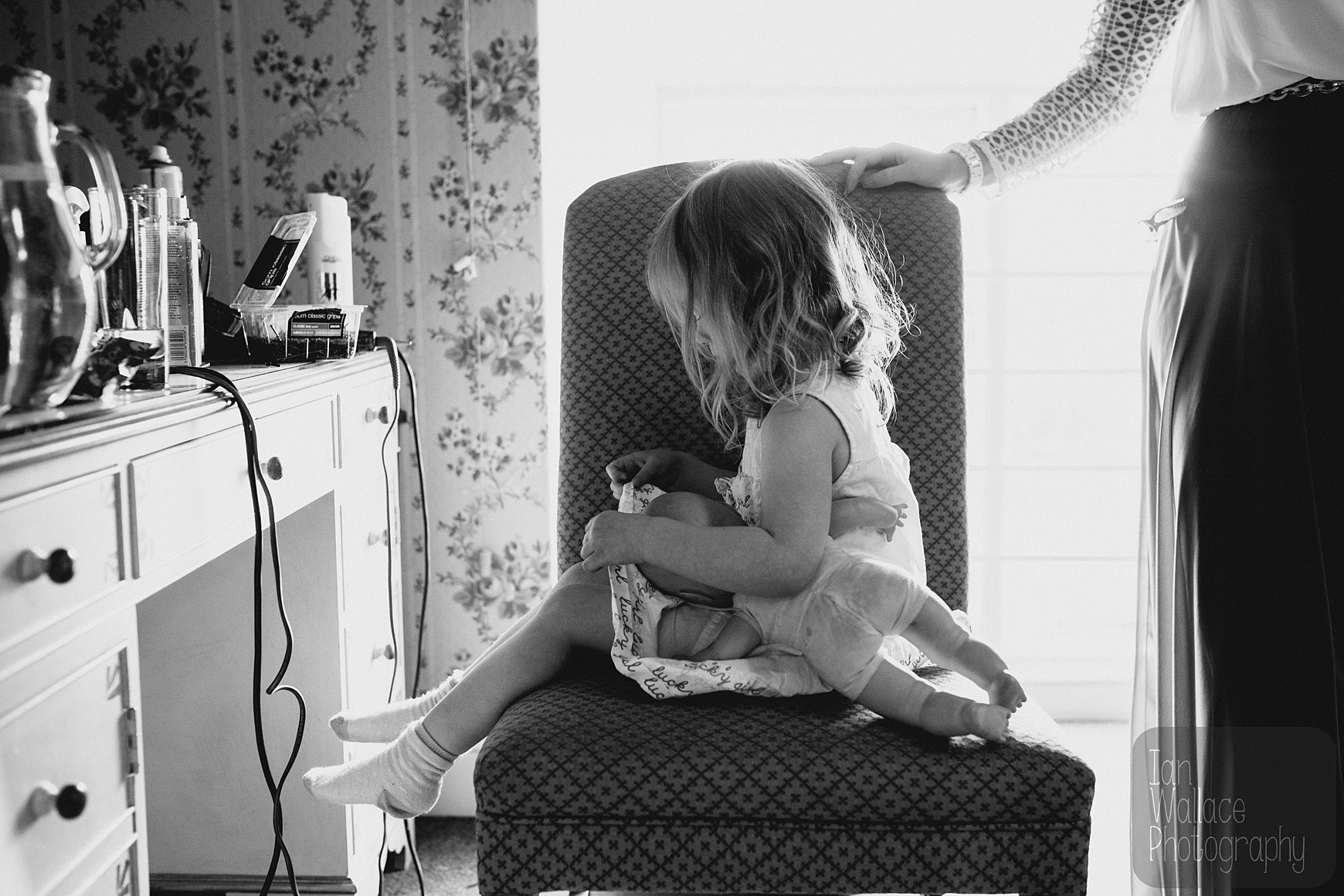 Flower-girl sits down with her doll ready for her hair doing