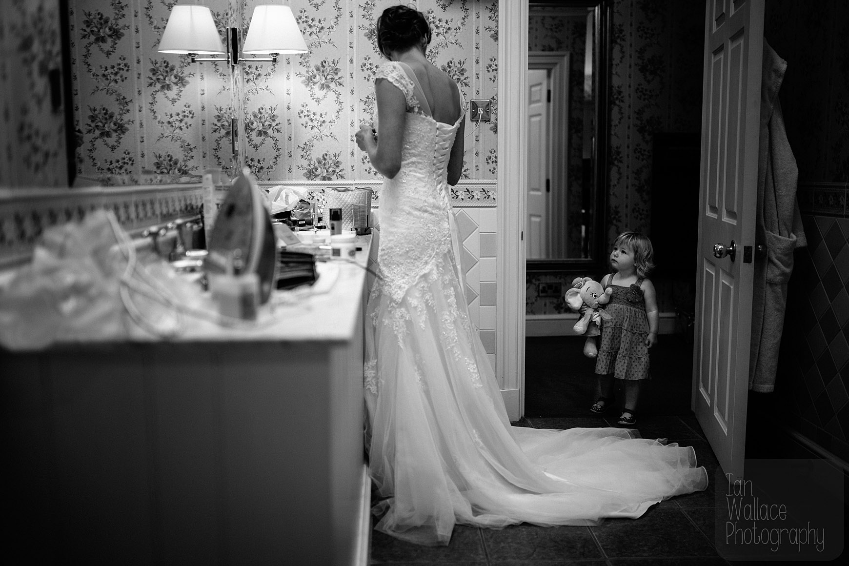 A little girl watches on as the bride finishes getting ready