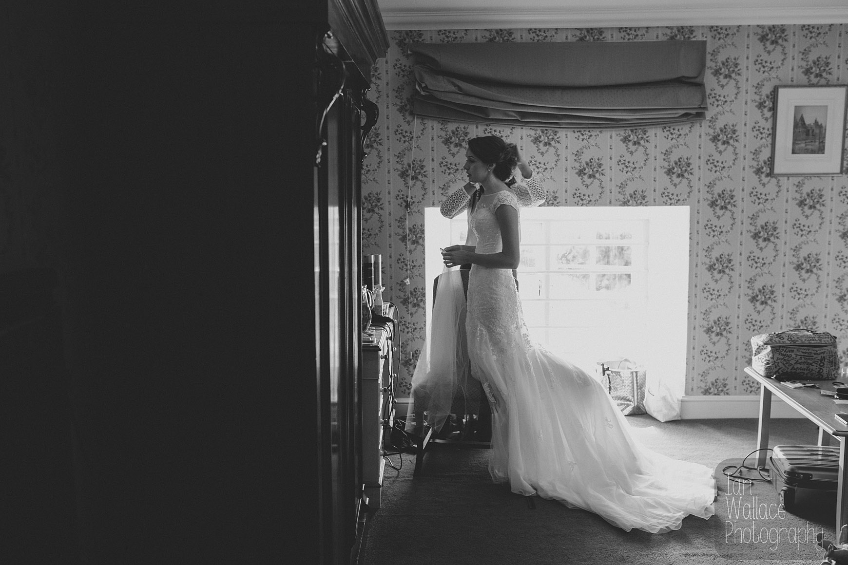 Fine art documentary image of a hairdresser putting the finishing touches to a bride