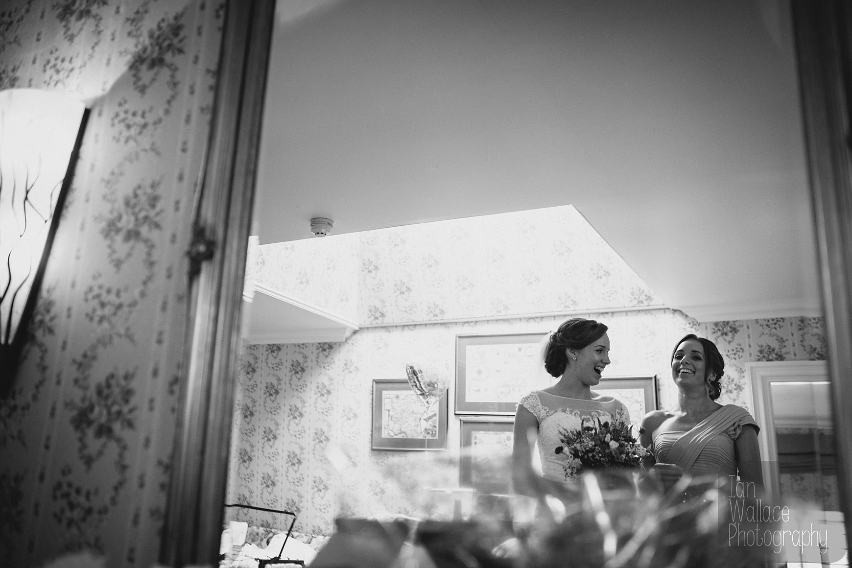 Bride and bridesmaid share a moment, laughing during the final build up