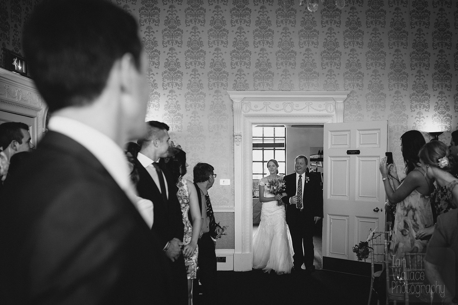 The bride enters the room with her father.