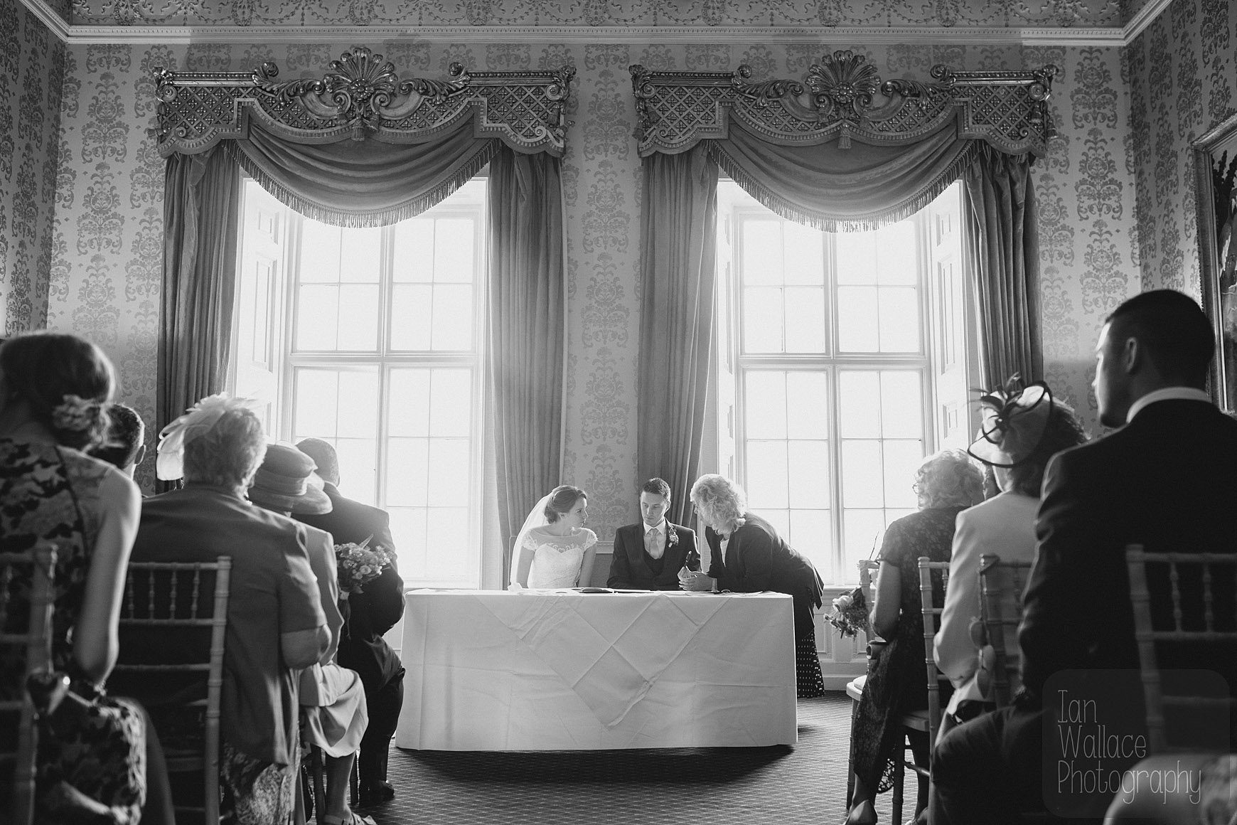 The registrar talking to the happily married couple as they sign the register.