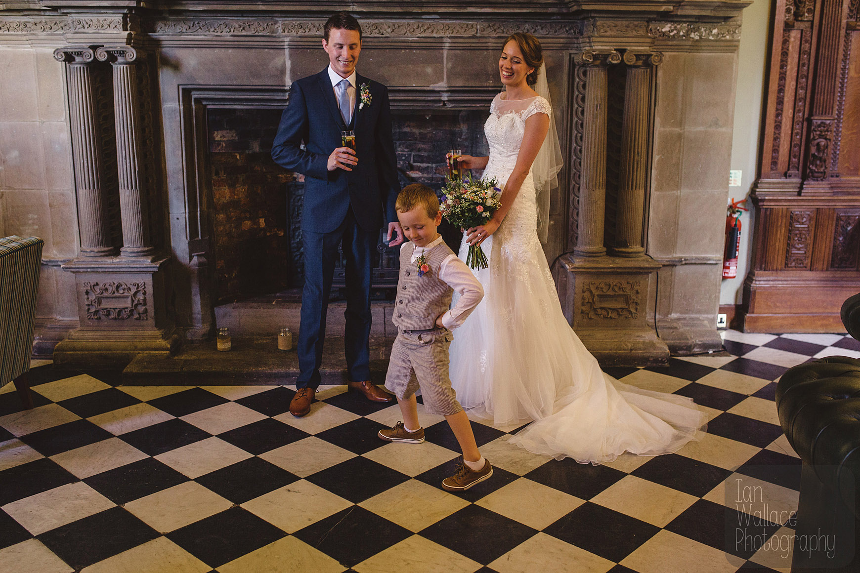 Newly married couple laugh as boy poses in front of fireplace