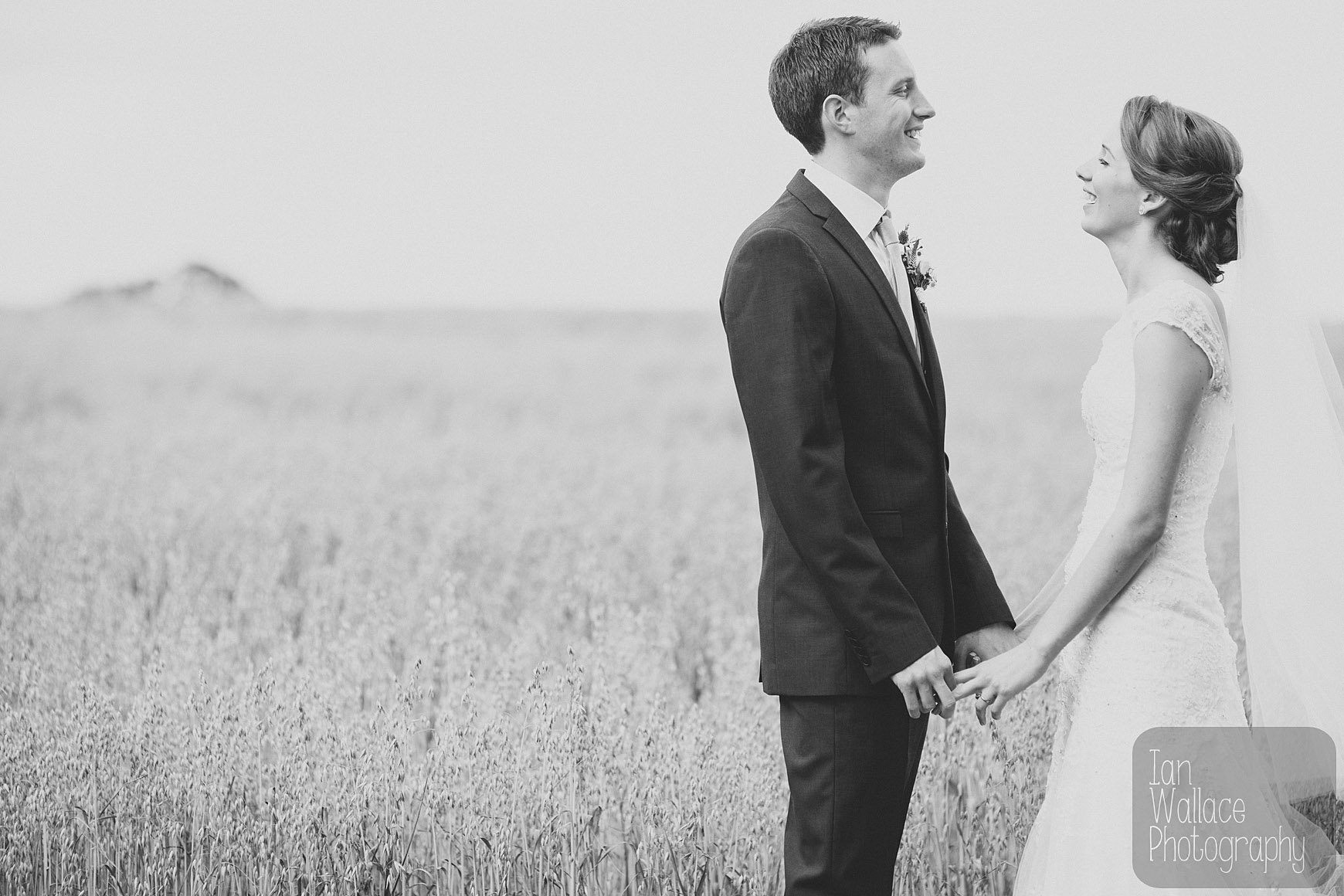Reportage fine art photo of couple laughing away from wedding party.