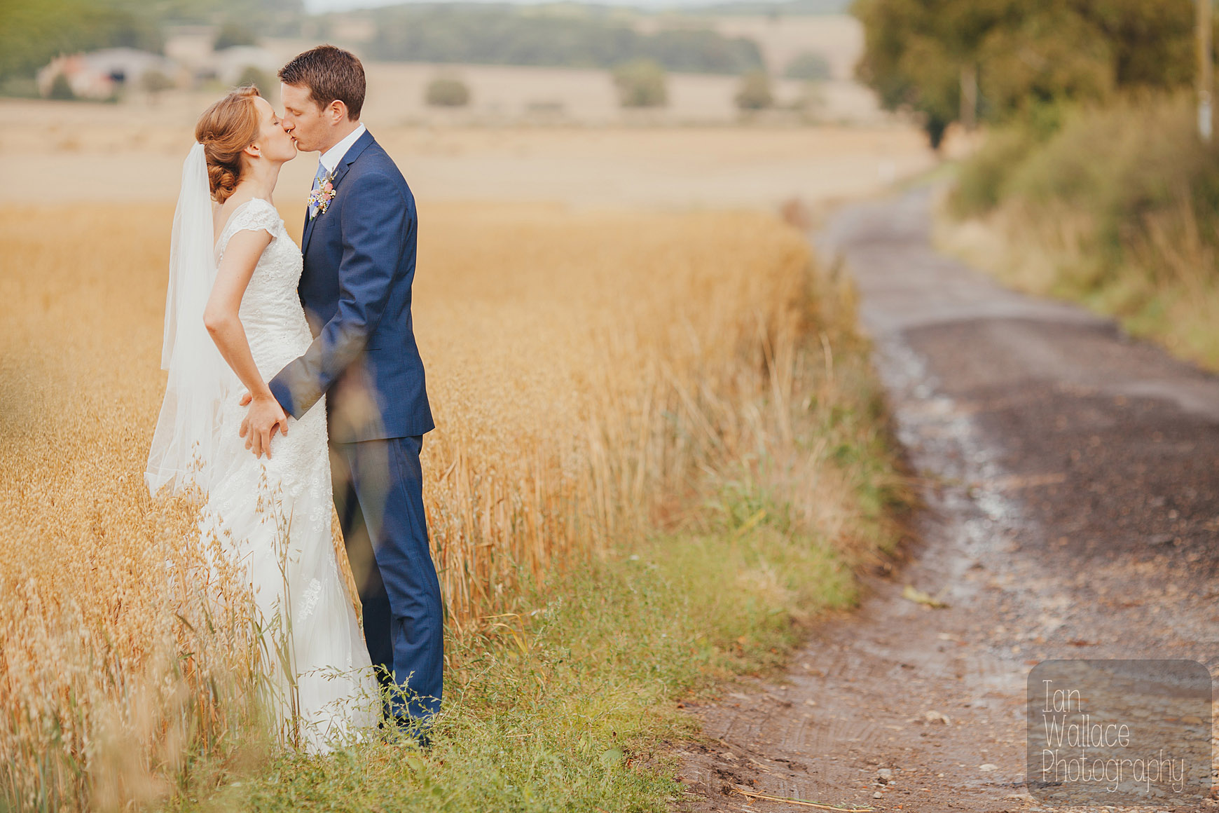 Couple kissing against a corn field and a dirt track