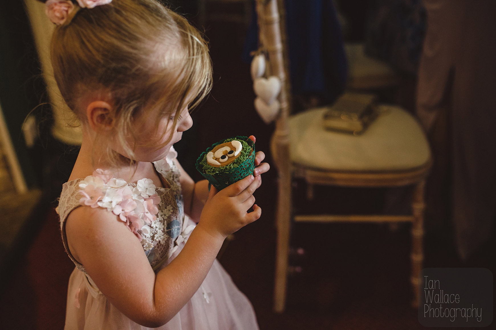 Flower-girl studying her cup cake which is about to be devoured.