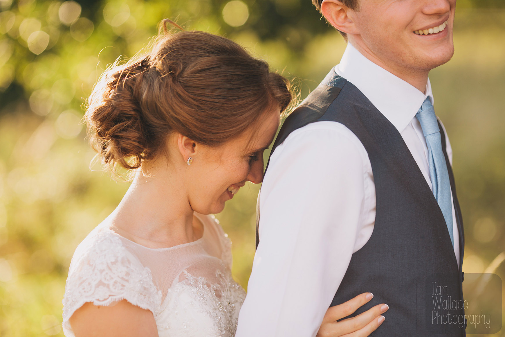 Bride and groom laughing during posing for portraits