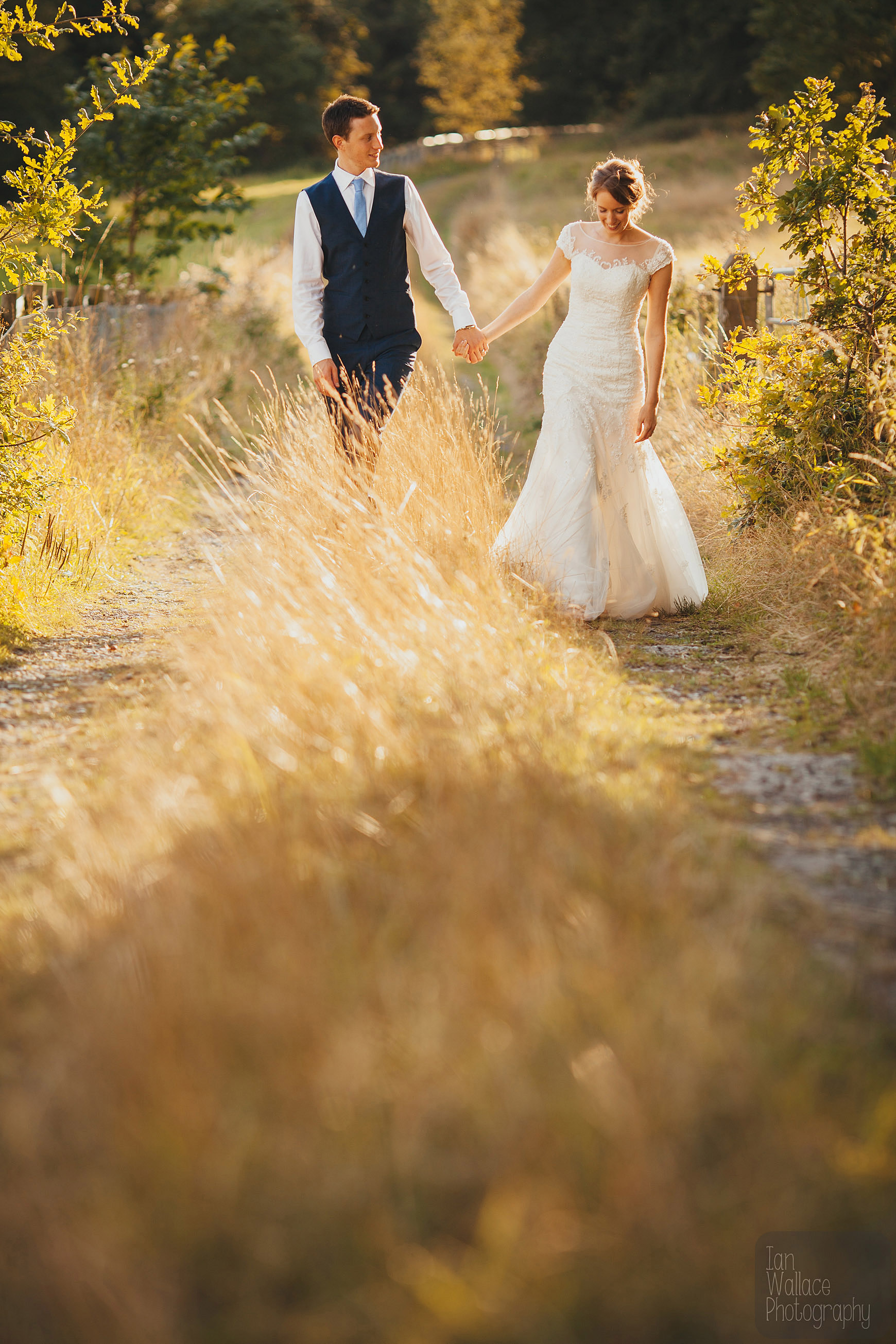 Beautifully lit portrait of newly weds walking along an overgrown dirt track.