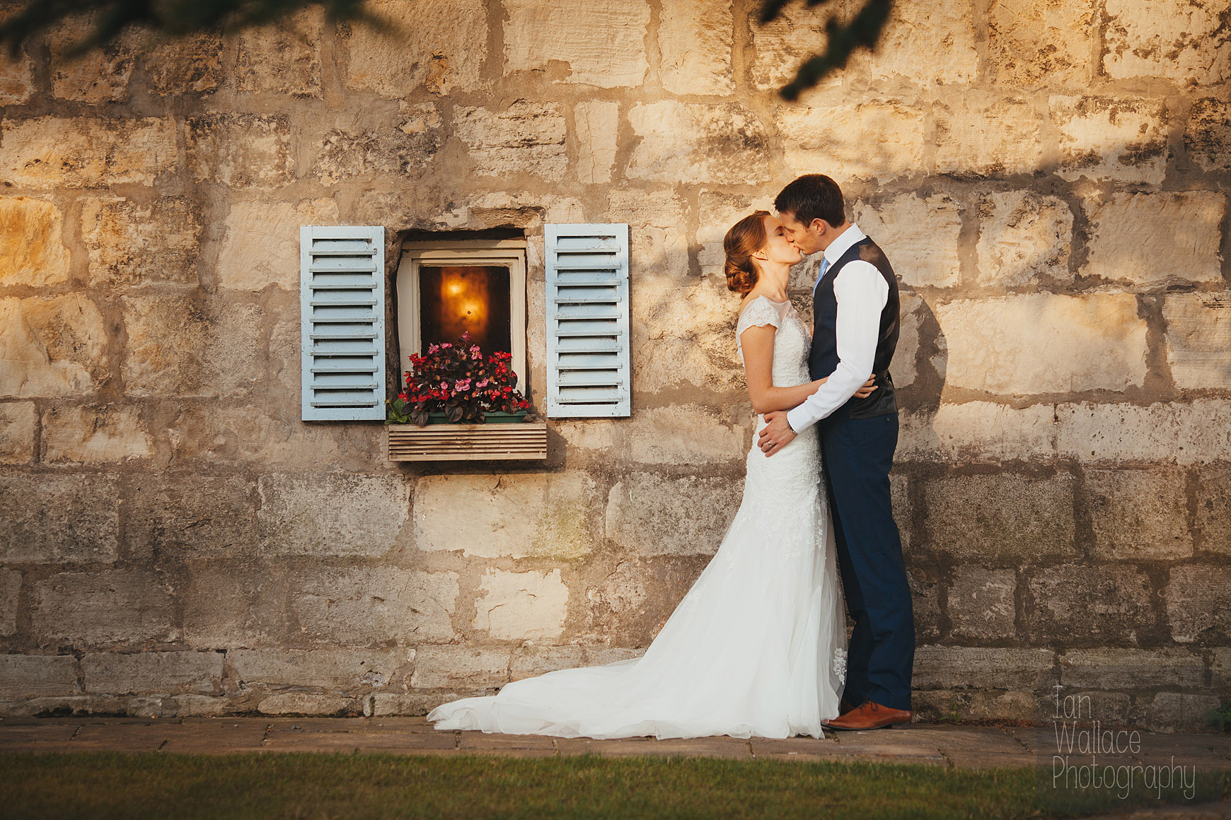 Couple embracing against a castle wall by a cute window
