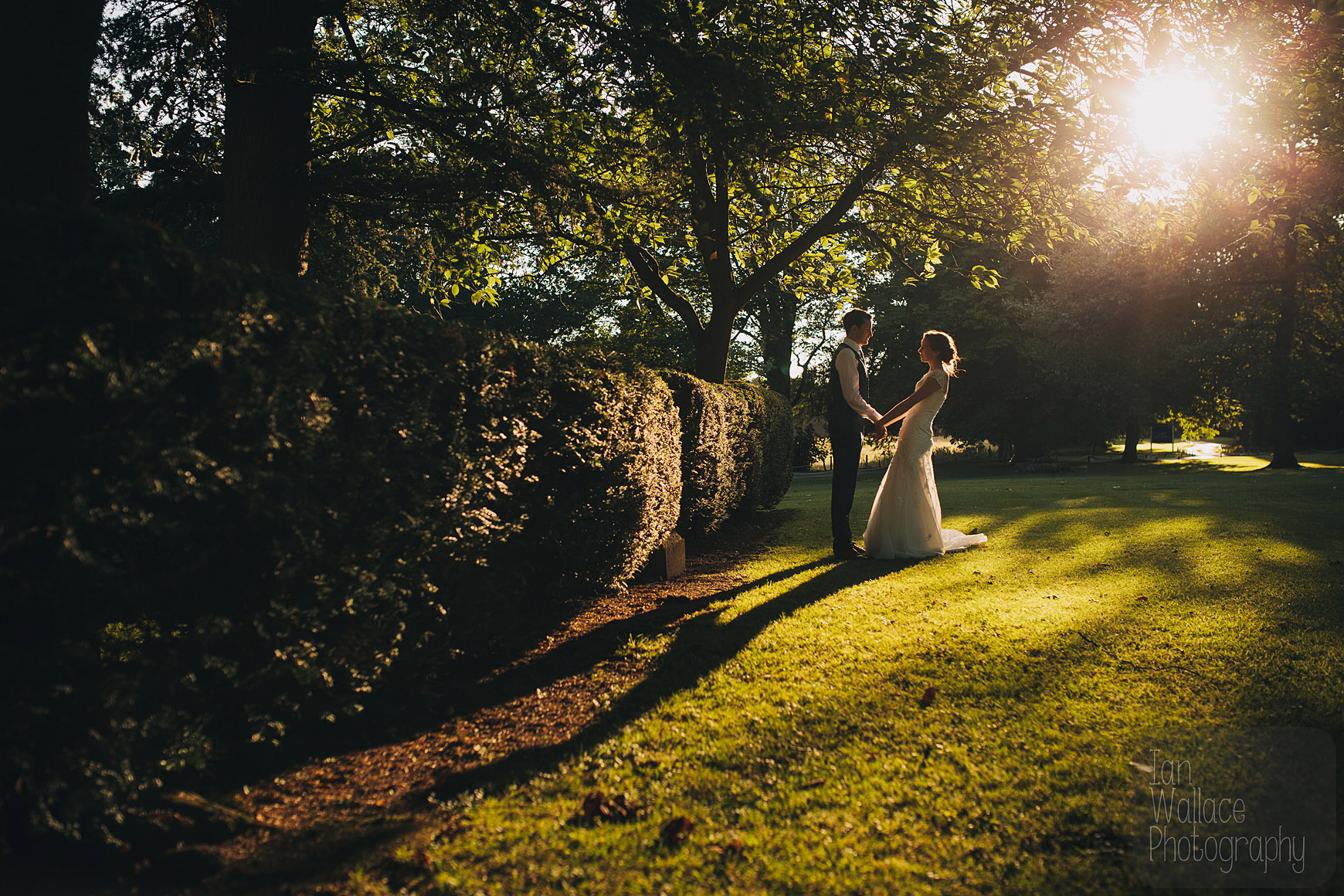 Bride and groom holding hands against a beautiful sunset backdrop.