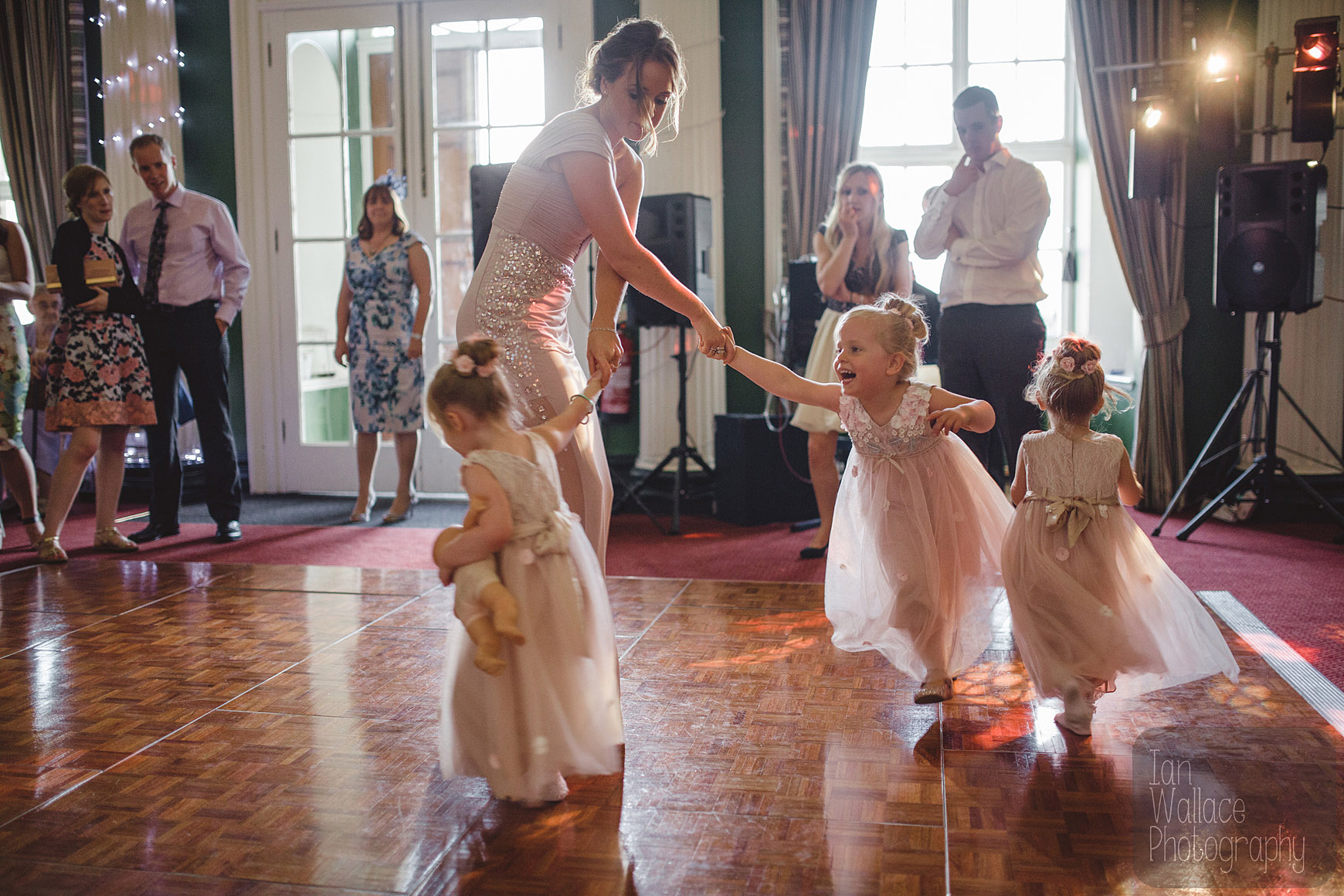 Bridesmaid dances/gets pulled around by the flower-girls at the disco.