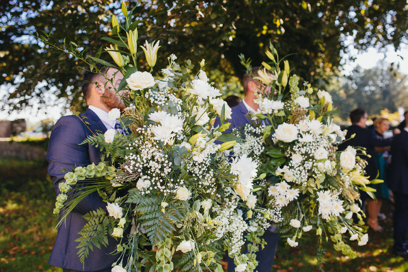 Grooms men moving the flowers documentary wedding photography