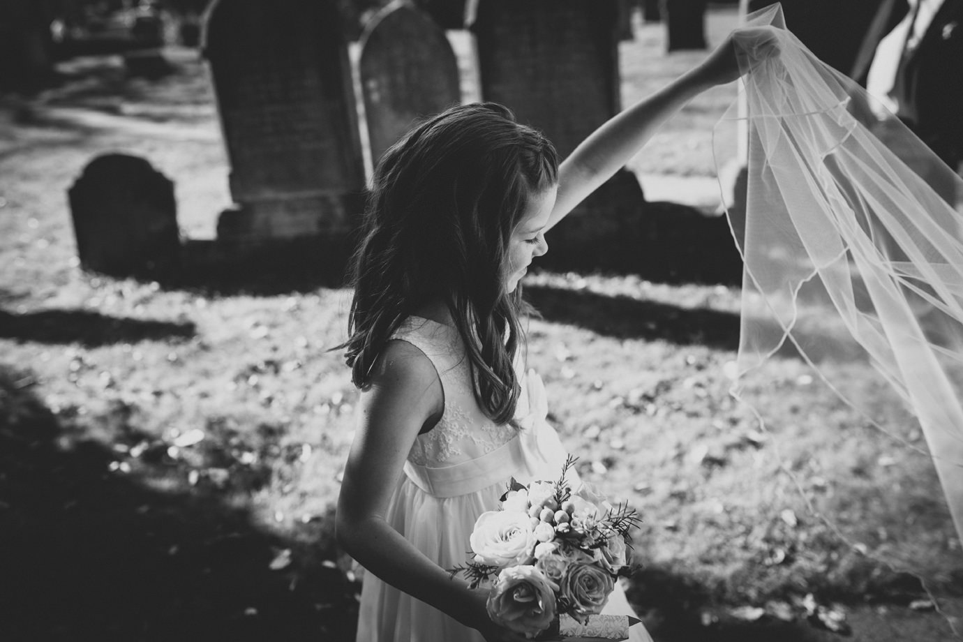 Flowergirl playing with the brides veil alternative wedding photography