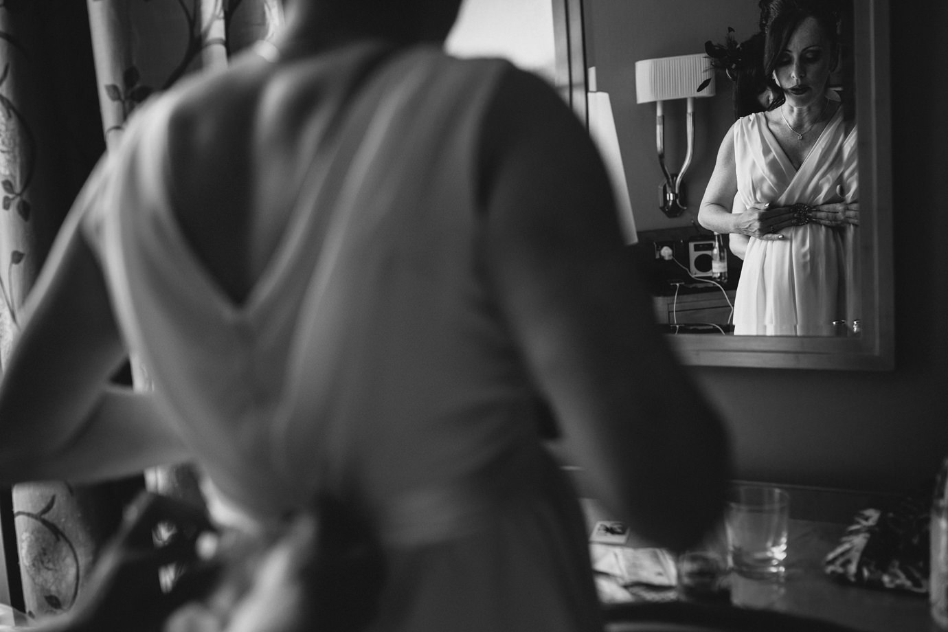Checking the dress, checking the bump. Pregnant bride, documentary wedding photography