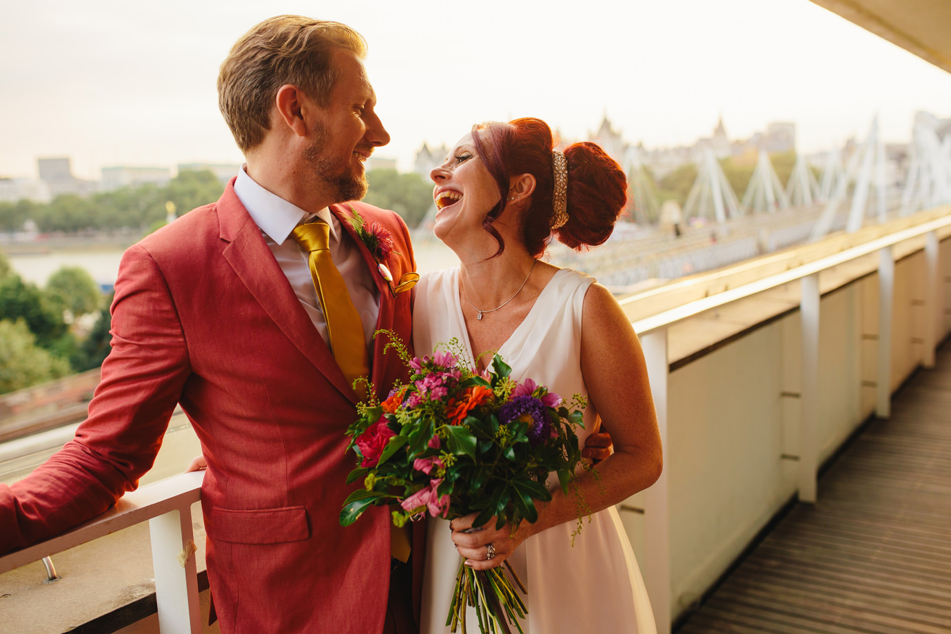 Happy newly wed couple on balcony overlooking Southbank in London, wedding photography